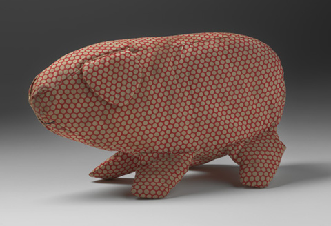 A soft toy in the shape of a pig made from off-white spotted red cotton fabric. The pig has a triangular ear and is missing its tail. A curved mouth is sewn onto the fabric in black thread.
