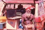 An Aboriginal man sits on the tailgate of a stationwagon. The man, who has a long beard, red headband and wears no top,is facing the photographer wearing a pair of trial spectacles. An open tray of lenses sits on a wooden box on the tailgate beside him.