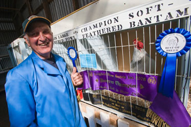 A man wearing a blue dust coat and a cap stands beside a crowing bantam, in a cage.