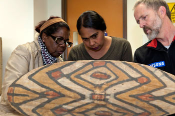 Two women and a man examine an indigenous bark shield.