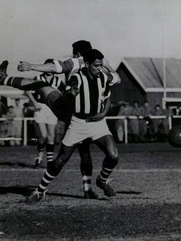 Black and white photo showing a man behind a partially visible soccer ball, with a member of the opposing team standing directly behind him.