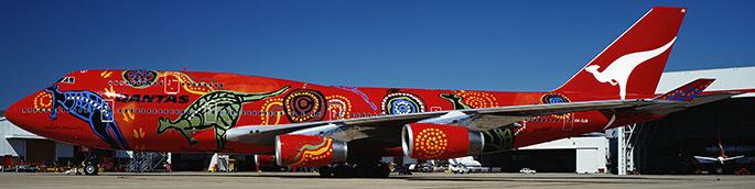 Side view of a large plane with Aboriginal designs painted on a red background.