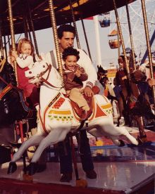 An image of children on a carousel ride.  Featured in the foreground is small boy on a carousel horse with a man standing behind him.