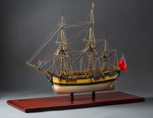 Small mounted model of a sailing ship with three masts.
