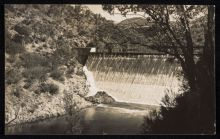 Black and white postcard showing a photograph of a concrete spillway, above a waterway. Gum trees line the steep bank on the left side.