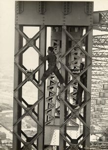 A man stands astride two sections of metal bridgework. He wars overalls and shoes without socks. Another man stands smiling while resting on another section of bridge at right.