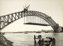 Black and white photograph of the partially constructed Sydney Harbour Bridge, with part of the road deck hanging below the main arch.