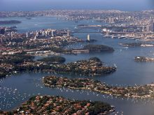 An aerial view of Sydney Harbour with the bridge and opera house at centre. Many small boats are moored in the foreground.