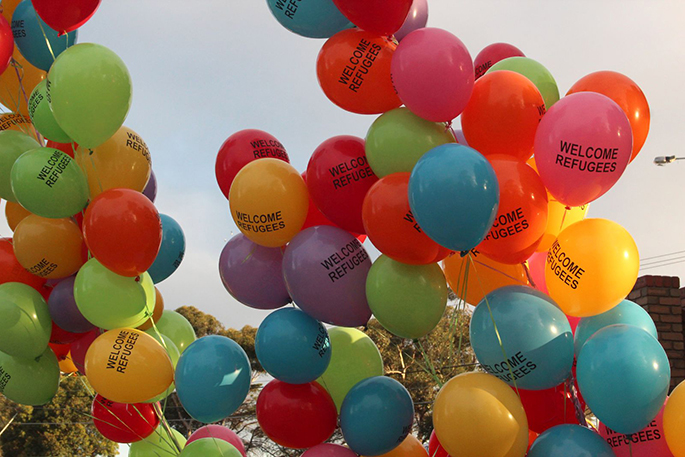 Multicoloured balloons with 'Welcome Refugees' on them flying in the air