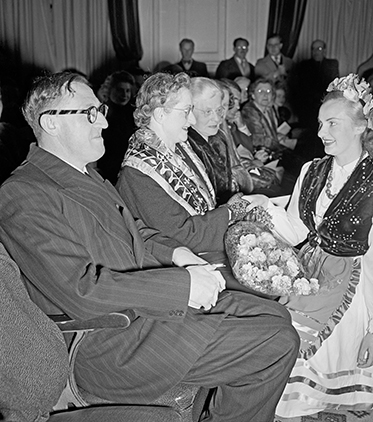 The Calwells seated with a woman in traditional Lithuanian dress shaking hands with Mrs Calwell.
