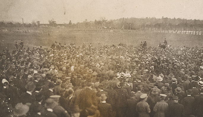 Grainy, poor-quality photo of a large crowd of men at an open expanse of grassland.