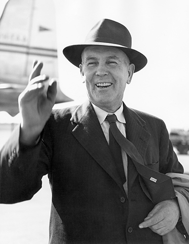 Chifley on the tarmac of an airport, smiling and waving.