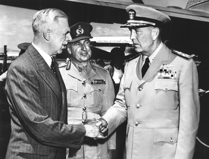 man in suit shakes hands with US admiral in uniform while New Zealand general looks on