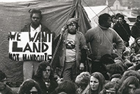 Aboriginal man standing in front of tent holding up sign saying �We want land not handouts�. He is surrounded by a dozen or so other protesters.