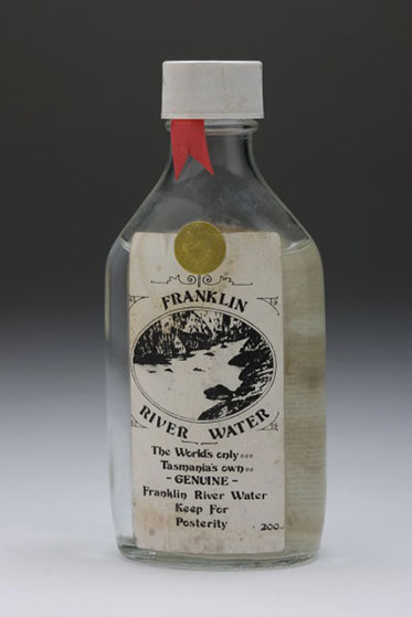 studio shot of bottle of water with a dirty label reading Franklin River water. The world's only. Tasmania's own. Genuine Franklin River Water. Keep for posterity. 200 ml