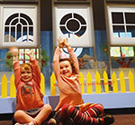 two brightly dressed children sitting on a floor with their legs crossed and their arms stretched up above their heads. Behind them are three white, differently shaped window props.