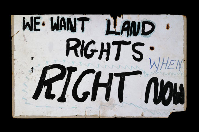White sign with the words 'We want land rights. When. Right now' hand painted in black.