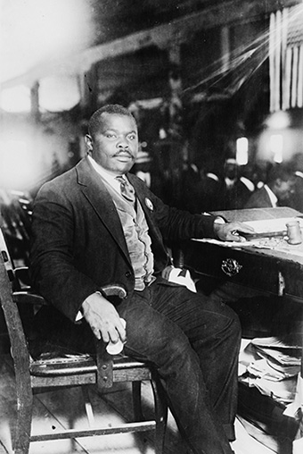 African man in a three-piece suit seated at a desk, looking at the camera