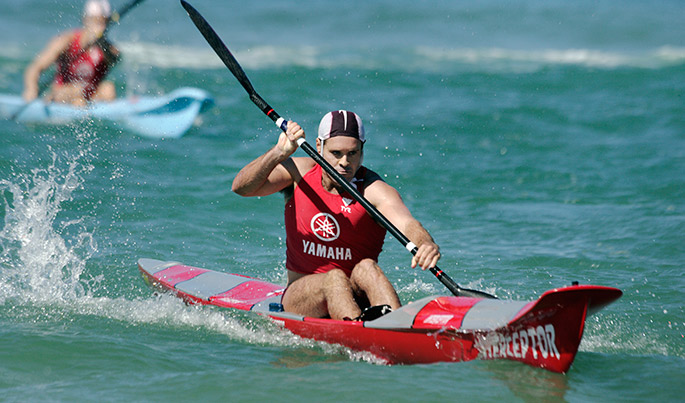 man in red singlet with Yamaha printed on it paddles a surf ski. Another competitor is visible behind him