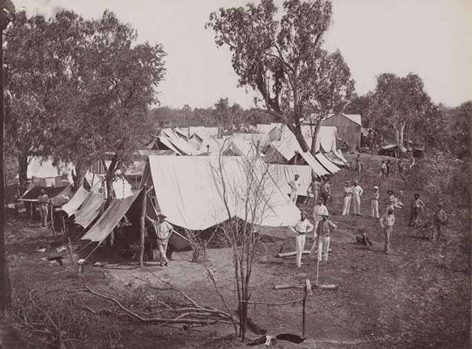 A black and white photo taken in the 1870s of a campsite