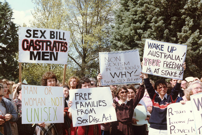 colour photo showing women and a couple of men protesting. Many are holding placards saying things like 'Sex bill castrates men', 'Free families from Sex Disc Act', 'Wake up Australia! Your freedom is at stake'