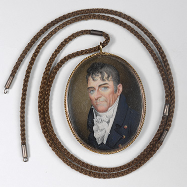 miniature portrait with necklace attached. The portrait depicts a man wearing a blue coat and a flouncy cravat. He has blue eyes and black wavy hair.