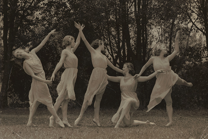 Five ballerinas dressed in white dresses perform on what appears to be grass with trees in the background
