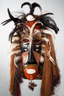 Cultural mask with black and ochre tones, feathers, and other materials.