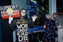 Man wearing a gas mask and clothing displaying words of protest