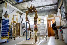 Large replica dinosaur leg bones suspended from above.