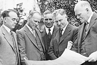 Group of men inspecting plans