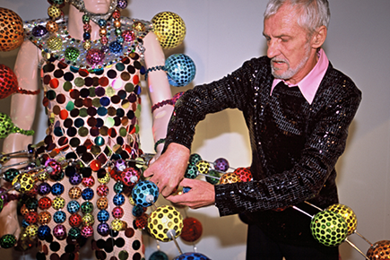 Man in sequined top adjusting colourful adornments on a costume that is worn by a mannequin.