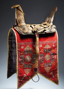 A saddle and saddlecloth with harness straps made from wood, leather, felted wool, wool embroidery