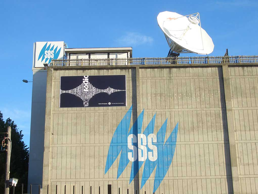 the outside of a large building which has a large white satellite dish and SBS logos on the side of the building.