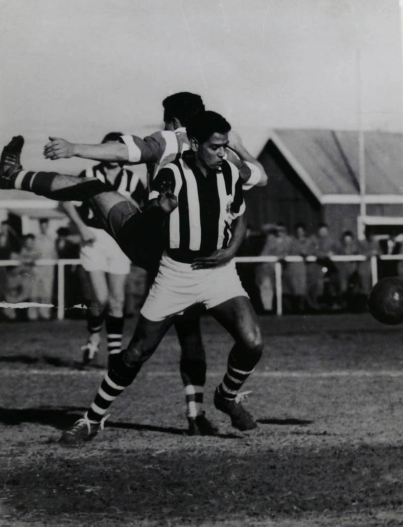 Black and white photo showing a man behind a partially visible soccer ball, with a member of the opposing team standing directly behind him. - click to view larger image