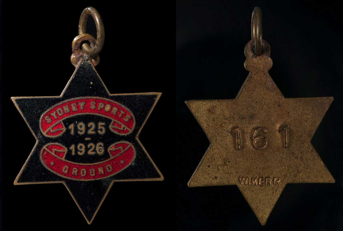 A six pointed star shaped black and red enamel medal with text on the front and back. - click to view larger image