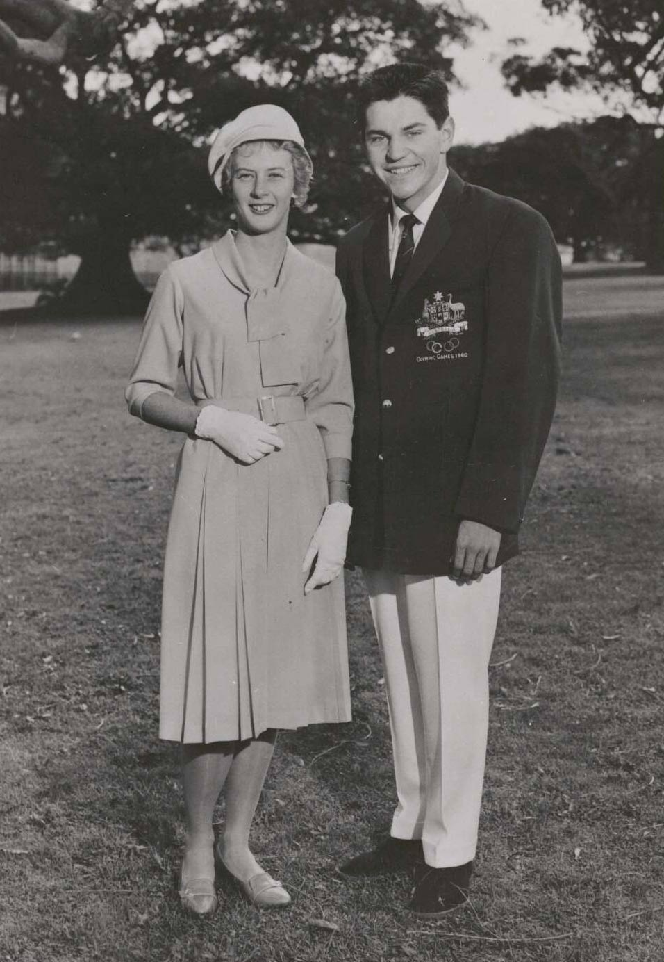 Black and white portrait showing a woman dressed in a knee-length dress and wearing a soft hat, gloves and shoes. A man stands to her right. He wears a dark blazer with an Australian coat of arms on the right breast pocket. He is also wearing a dark necktie, light-coloured trousers and dark shoes. - click to view larger image