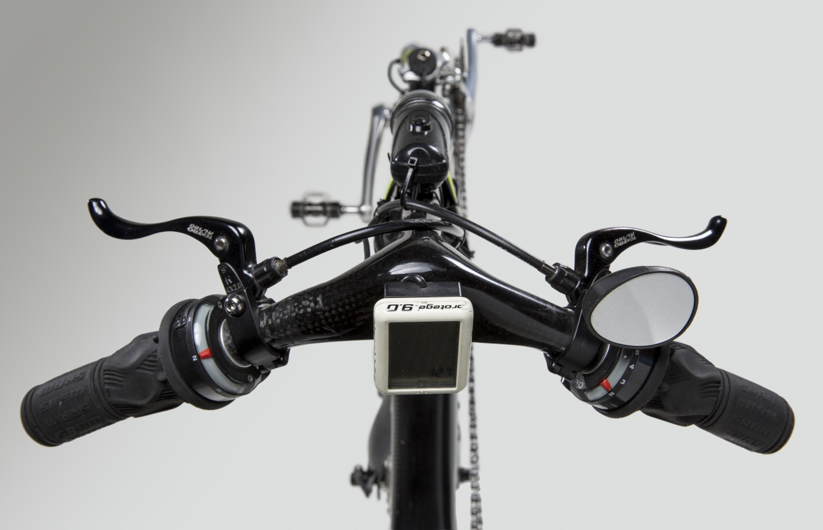 Colour photo, taken from above, showing a close up view of a bike's handlebars, with rubber handgrips and rear vision mirror. - click to view larger image