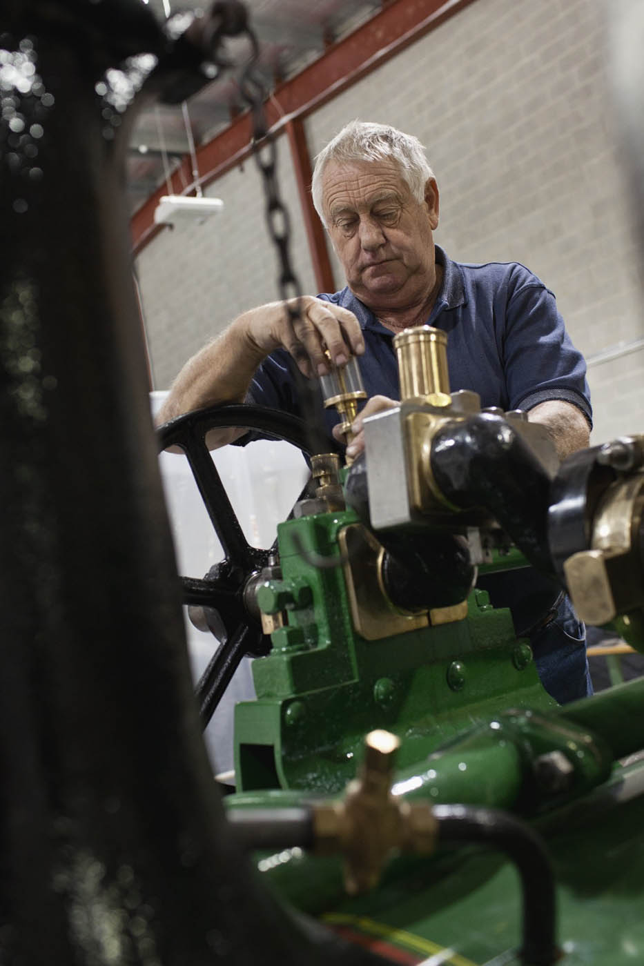 A colour photograph of a man working on an oil gauge. - click to view larger image