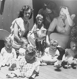Black and white photo of three young mothers with six young children.