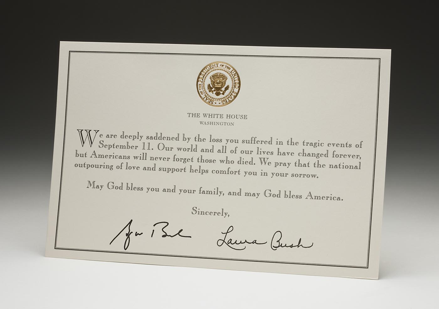 A beige-coloured card with a gold seal at centre top, with printed text 'THE WHITE HOUSE / WASHINGTON'. At the centre is the printed text: 'We are deeply saddened by the loss you suffered in the tragic events of September 11. Our world and all of our lives have changed forever, but Americans will never forget those who died. We pray that the national outpouring of love and support helps comfort you in your sorrow. May God bless you and your family, and may God bless America. Sincerely,'. The card has two handwritten signatures centre bottom, 'George Bush' left and 'Laura Bush' right.