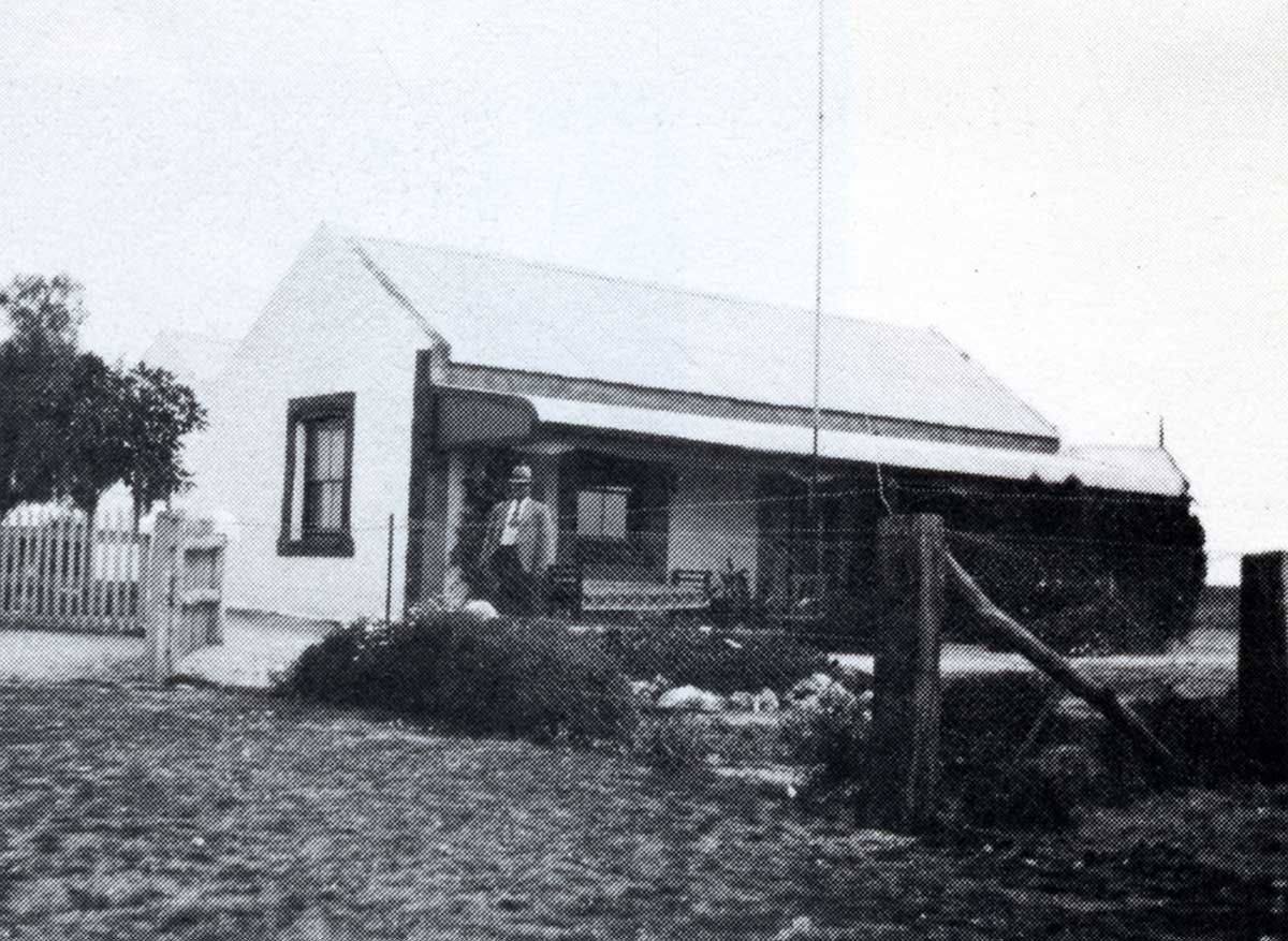 Black and white photo showing a man standing at the front of the small homestead, with a picket fence to the left and a fenced garden at the front. A daybed and wooden chair are on the verandah.