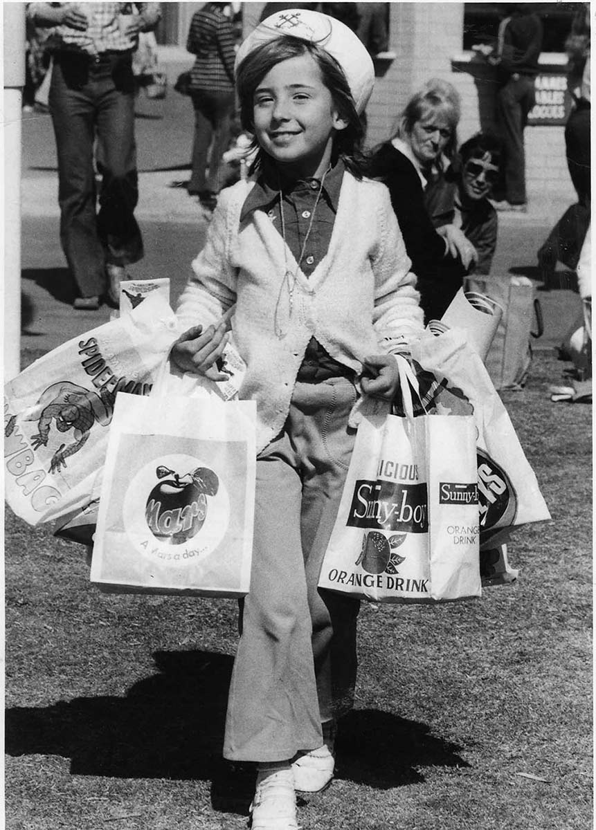 Black and white photo of a child wearing a sailor's hat and pants and carrying mulitple show bags on both arms. - click to view larger image