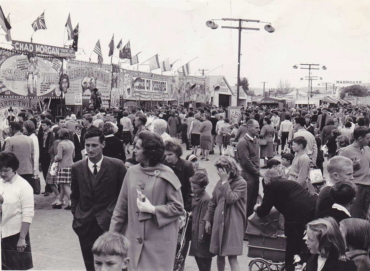 A large crowd of people with many gathering outside tents and buildings with signs advertising 'Chad Morgan', 'Le-Garde Twins' and 'Maze of Mirrors'. Other people are walking down the centre of the alley. - click to view larger image