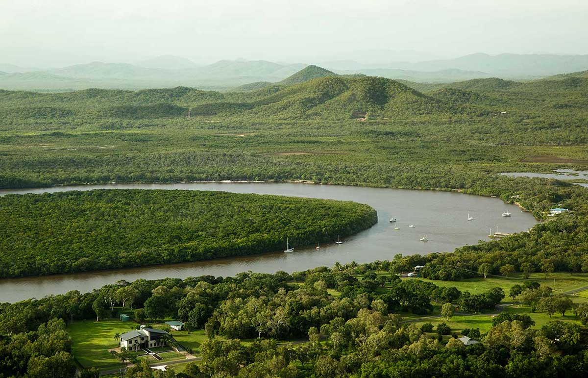 Aerial photograph of a river winding its way through lush green countryside. Several boats are moored on the river. - click to view larger image