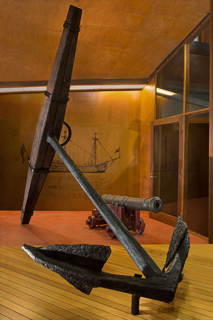 Museum display showing a metal ship's anchor with wooden stock. A cannon and diagram of a ship are also visible.