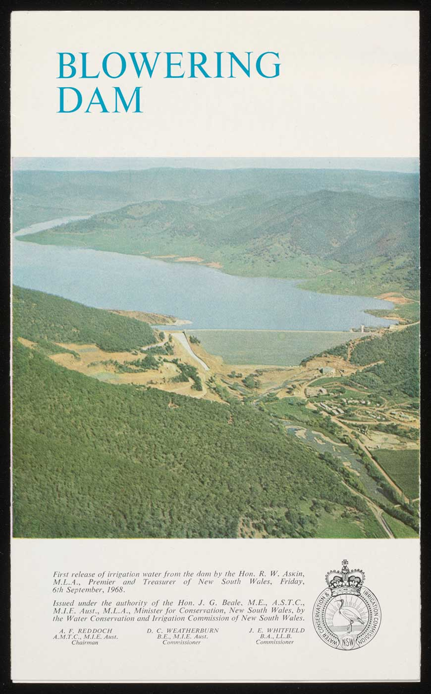 Cover of a booklet titled 'Blowering Dam' showing an aerial photo of a large dam and surrounding landscape. Text and a small crest also feature at the bottom. - click to view larger image