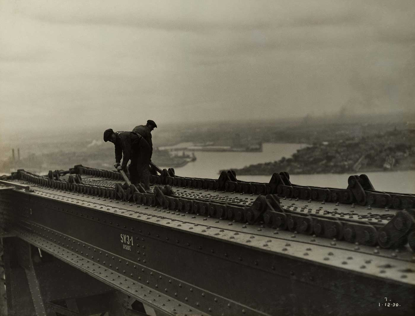 Two workers adjust the track for a 'creeper' crane atop a metal section of bridge. - click to view larger image