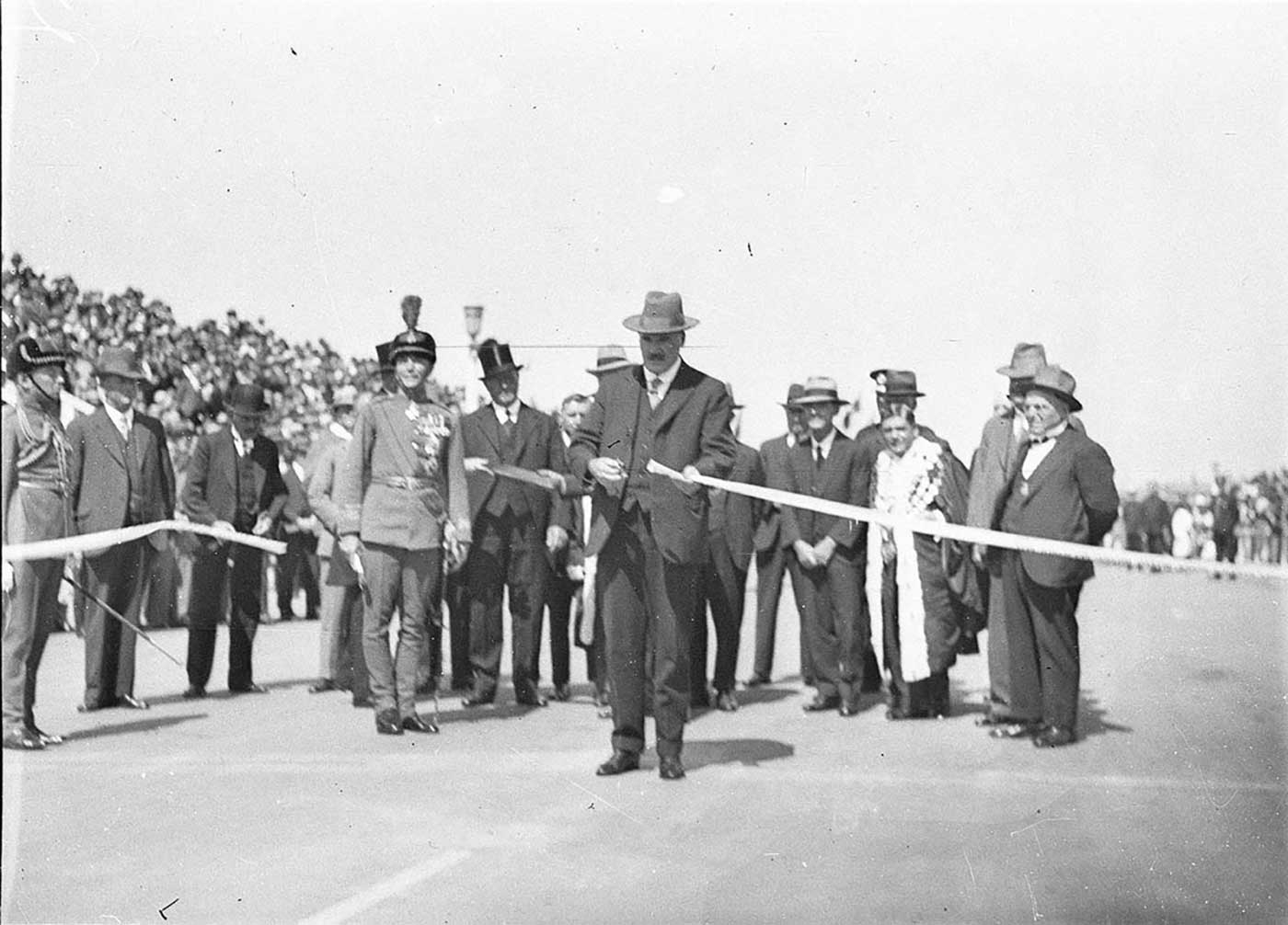 Black and white photo of dignitaries, with one man standing forward to cut a ribbon. - click to view larger image