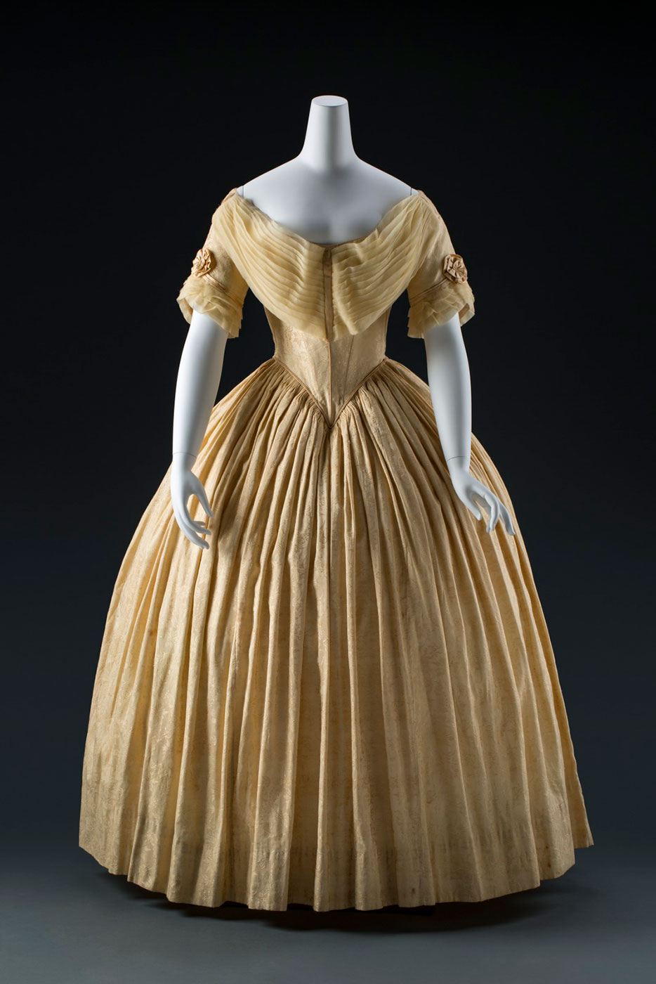 A pale yellow dress with full skirt and off the shoulder sleeves, displayed on a mannequin - click to view larger image